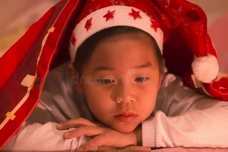 O menino vestiu um chapéu do Natal sob um geral, tristemente e apenas no imagem de stock