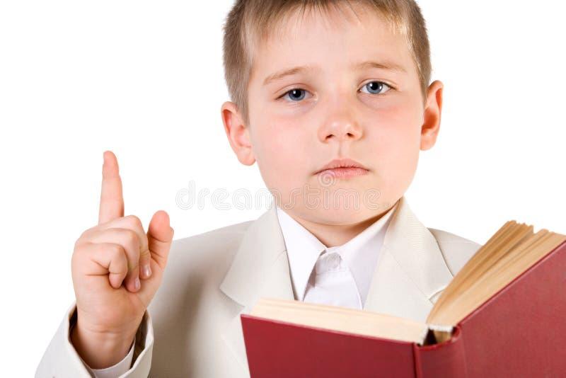 O menino Well-dressed leu o livro e levantou o dedo acima fotos de stock