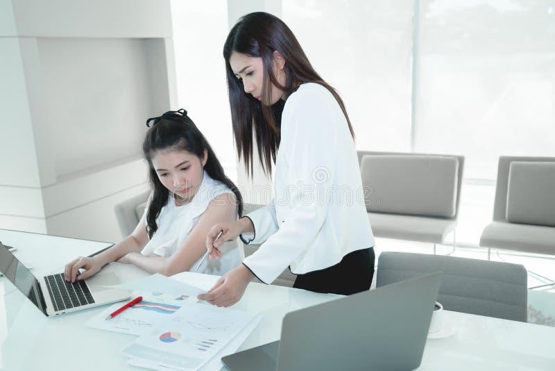 O mentor da mulher do colega que ajuda o trabalhador novo, jovens de ensino controla foto de stock