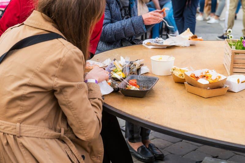 O mercado, o festival, o evento e comer de visita do alimento do grupo de pessoas traseiro da vista levam embora a refeição na pr fotografia de stock