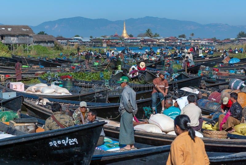 O mercado local está aglomerando-se com os barcos de fileira dos turistas e o birmanês no centro do lago famoso foto de stock