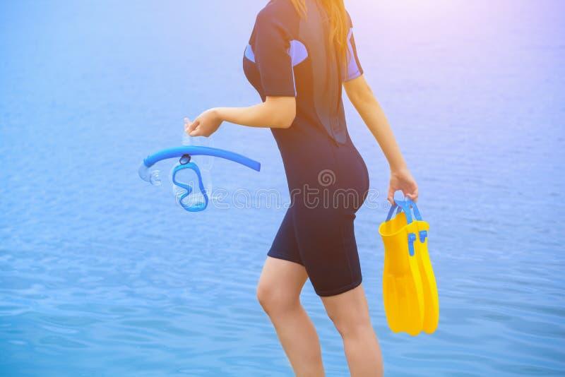 O mergulhador da menina em um terno molhado guarda uma máscara com um tubo azul em suas mãos e uma aleta amarela na outra mão fotos de stock royalty free