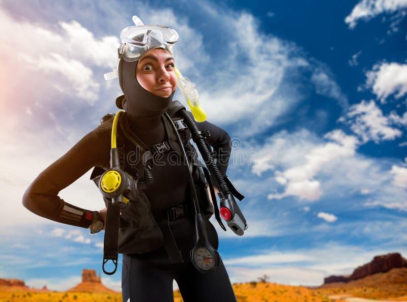 O mergulhador fêmea na engrenagem de mergulho levanta na praia foto de stock