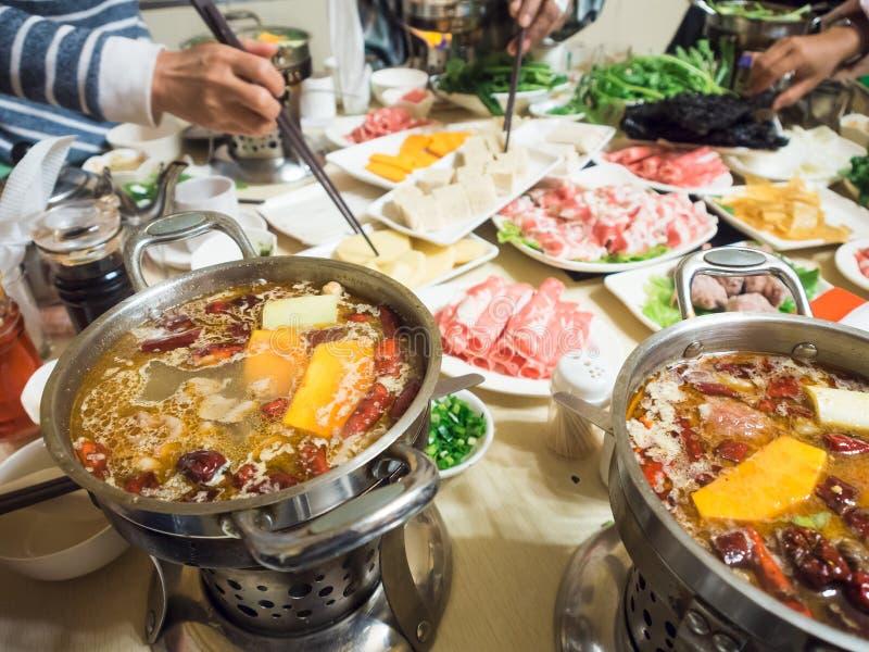 O mergulho dinning chinês cortou a carne na sopa quente dos pimentões imagem de stock