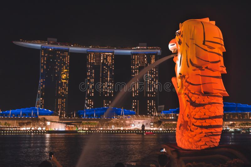 O Merlion com as listras do tigre que negligenciam Marina Bay Sands durante o iLight 2019 de Singapura fotografia de stock