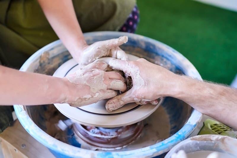 O mestre ajuda o estudante a fazer o potenciômetro da argila Ferramentas e roda do ofício dos oleiro foto de stock