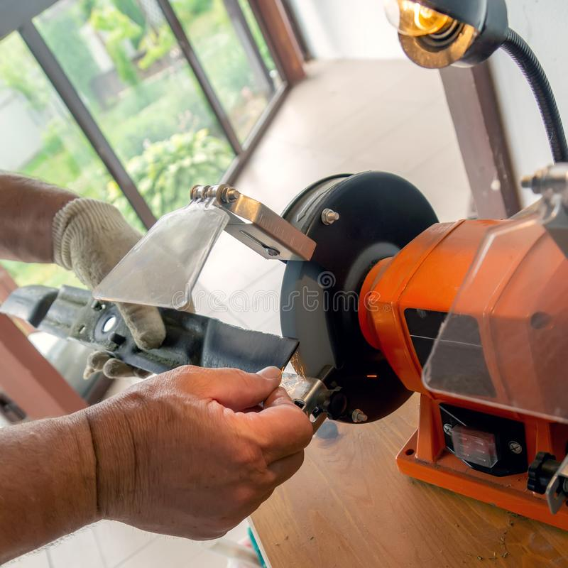O mestre aponta no cortador de grama da faca do metal da máquina A mão de mestre nas luvas brancas que guardam a placa de metal fotografia de stock