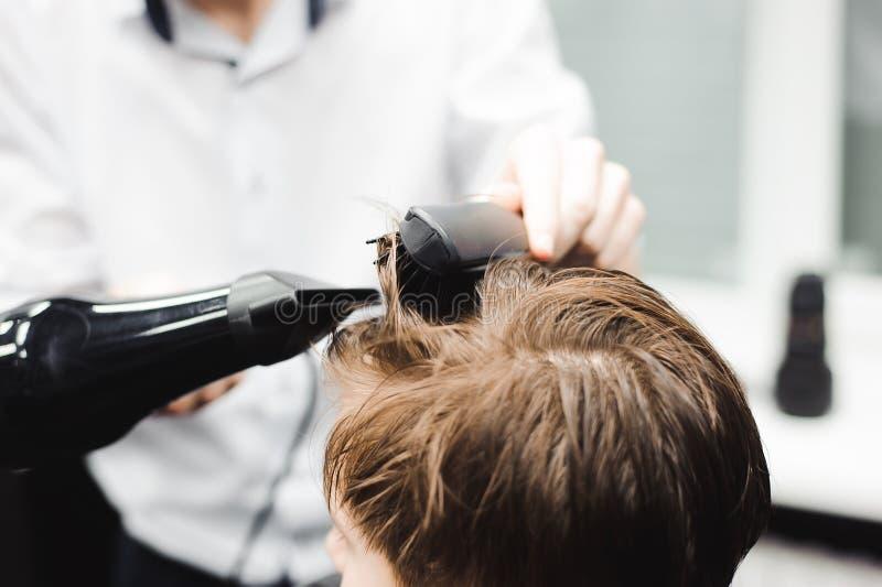 O mestre corta o cabelo de um menino no barbeiro, cabeleireiro faz o penteado para um menino imagens de stock