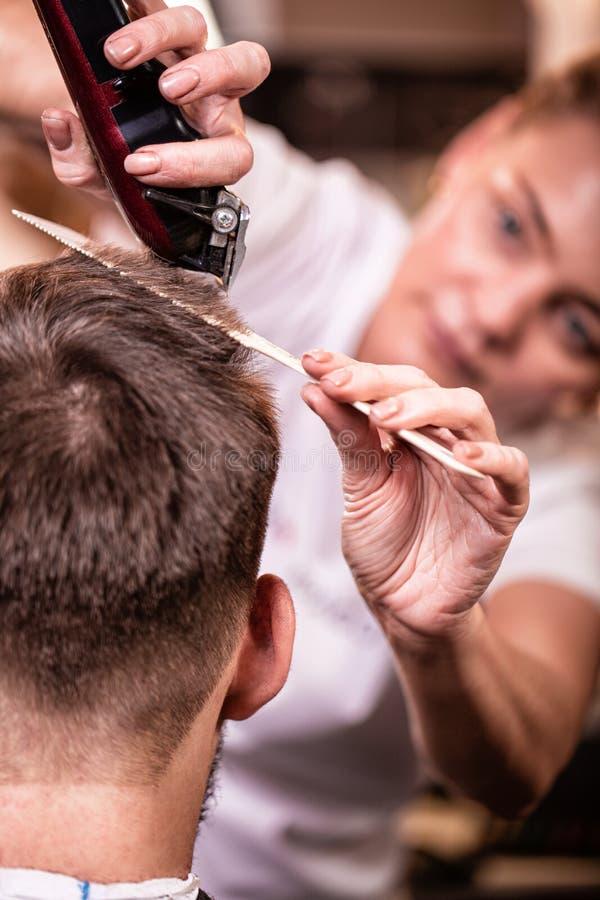 O mestre corta o cabelo e a barba de um homem em um barbeiro, um cabeleireiro faz um corte de cabelo para um homem novo beleza foto de stock