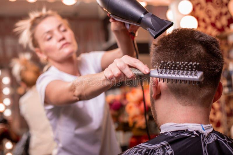 O mestre corta o cabelo e a barba de um homem em um barbeiro, um cabeleireiro faz um corte de cabelo para um homem novo beleza imagens de stock royalty free