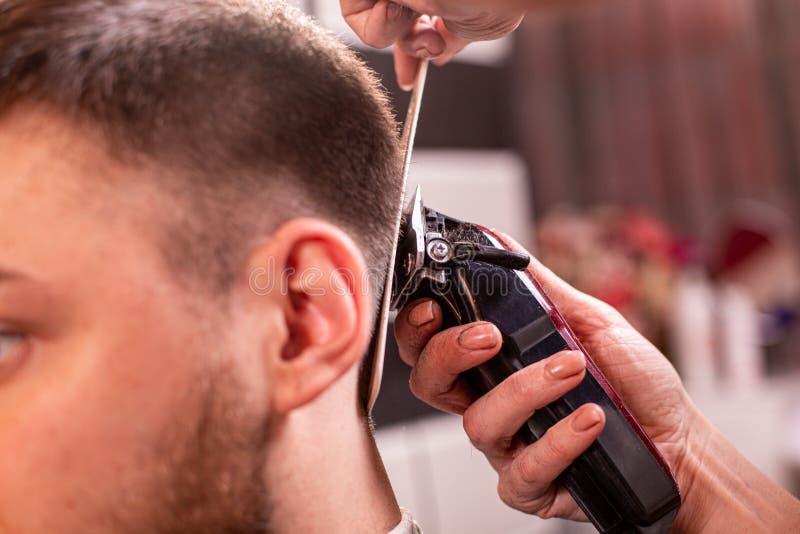 O mestre corta o cabelo e a barba de um homem em um barbeiro, um cabeleireiro faz um corte de cabelo para um homem novo beleza foto de stock royalty free