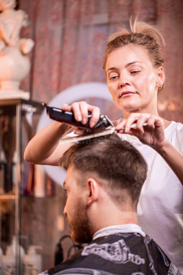 O mestre corta o cabelo e a barba de um homem em um barbeiro, um cabeleireiro faz um corte de cabelo para um homem novo beleza fotos de stock royalty free