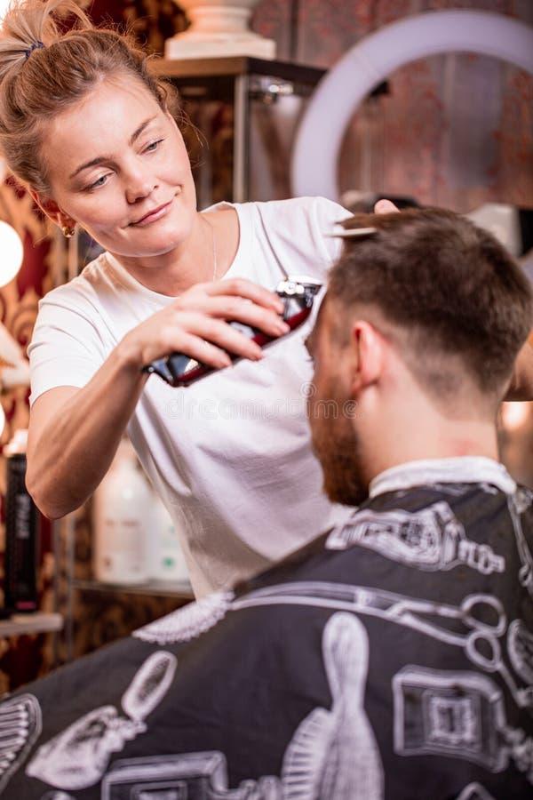 O mestre corta o cabelo e a barba de um homem em um barbeiro, um cabeleireiro faz um corte de cabelo para um homem novo beleza imagem de stock royalty free