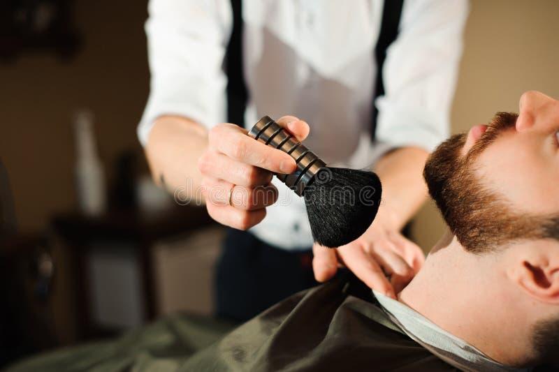 O mestre corta o cabelo e a barba dos homens no barbeiro fotografia de stock