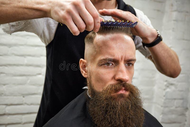 O mestre corta o cabelo e a barba dos homens no barbeiro, cabeleireiro faz o penteado para um homem novo imagens de stock