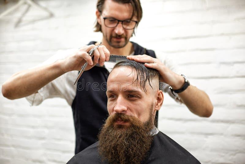 O mestre corta o cabelo e a barba dos homens no barbeiro, cabeleireiro faz o penteado para um homem novo foto de stock royalty free