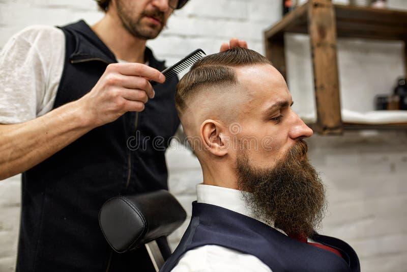 O mestre corta o cabelo e a barba dos homens no barbeiro, cabeleireiro faz o penteado para um homem novo fotografia de stock
