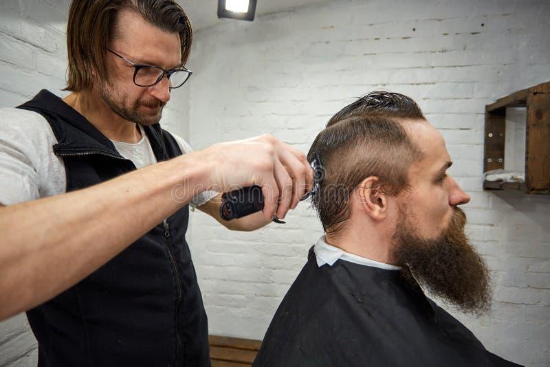 O mestre corta o cabelo e a barba dos homens no barbeiro, cabeleireiro faz o penteado para um homem novo fotos de stock