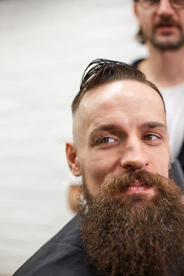 O mestre corta o cabelo e a barba dos homens no barbeiro, cabeleireiro faz o penteado para um homem novo imagens de stock royalty free