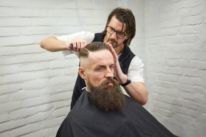 O mestre corta o cabelo e a barba dos homens no barbeiro, cabeleireiro faz o penteado para um homem novo imagem de stock