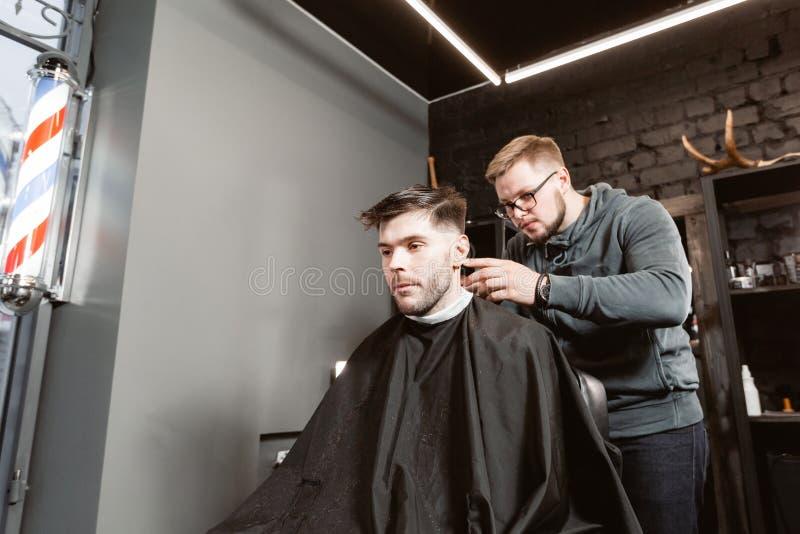 O mestre corta o cabelo e a barba dos homens no barbeiro, cabeleireiro faz o penteado para um homem novo E fotos de stock