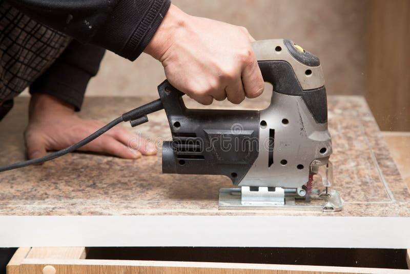 O mestre corta a madeira com uma serra do gabarito imagens de stock