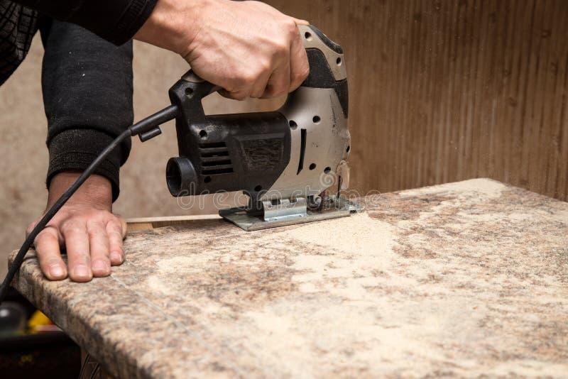 O mestre corta a madeira com uma serra do gabarito fotografia de stock
