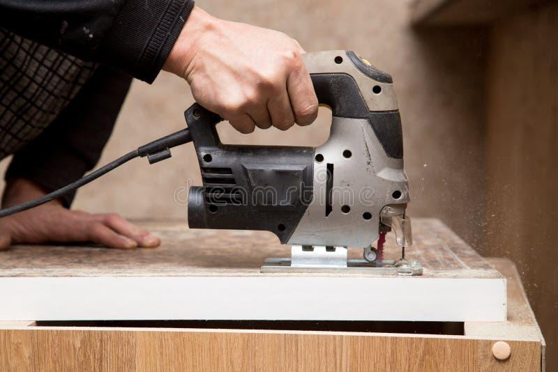 O mestre corta a madeira com uma serra do gabarito imagem de stock