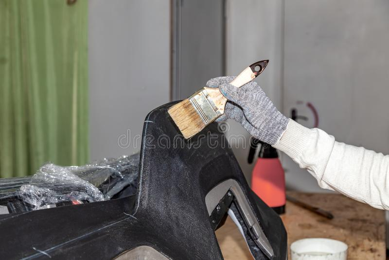 O mestre da cintura do carro que aplica a colagem com uma escova no painel plástico superior para colar o couro na oficina do pro imagem de stock