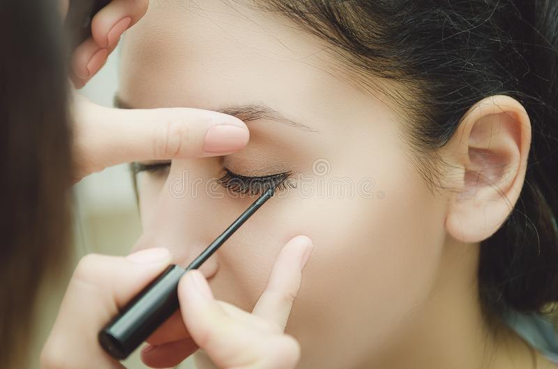 O mestre da composição pinta os olhos da menina Faz a composição, close-up fotos de stock