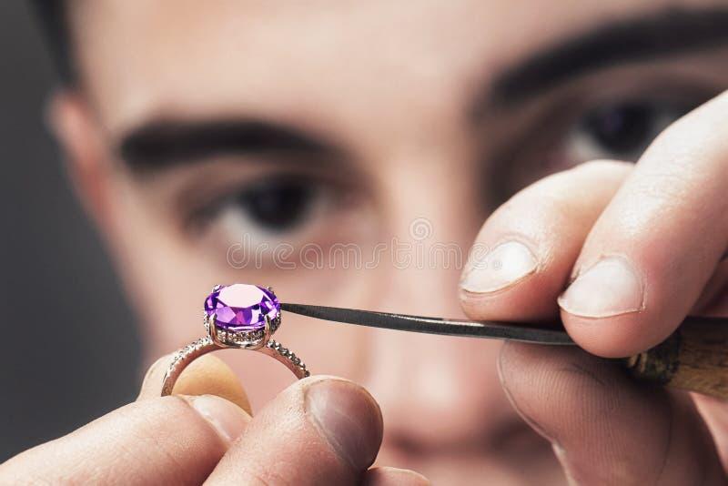O mestre da joia examina o anel de ouro para defeitos imagens de stock royalty free