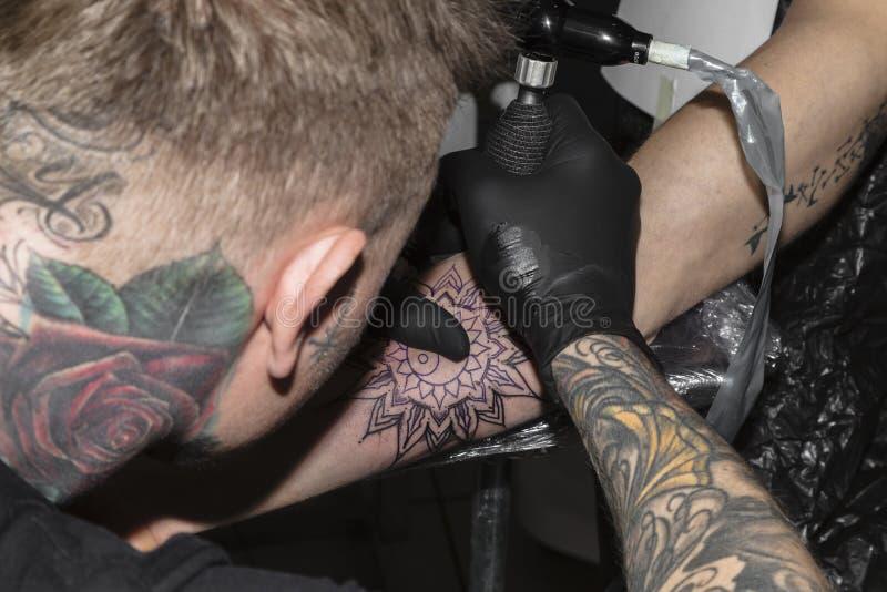 O mestre da tatuagem faz a tatuagem no formulário da mandala fotografia de stock