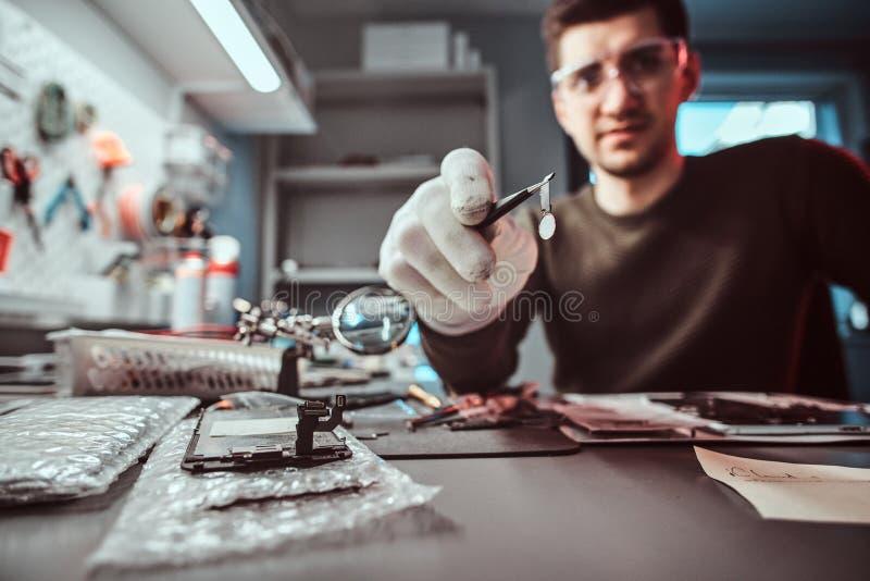 O mestre da tecnologia eletrônica guarda uma microplaqueta de tabuleta quebrada na oficina de reparações foto de stock royalty free