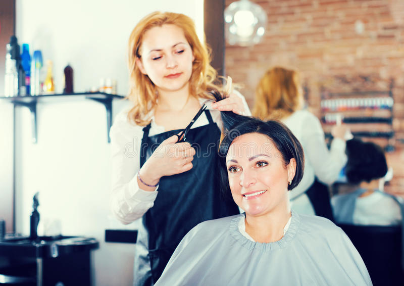 O mestre do corte de cabelo está fazendo o penteado e o corte por meio das tesouras imagem de stock
