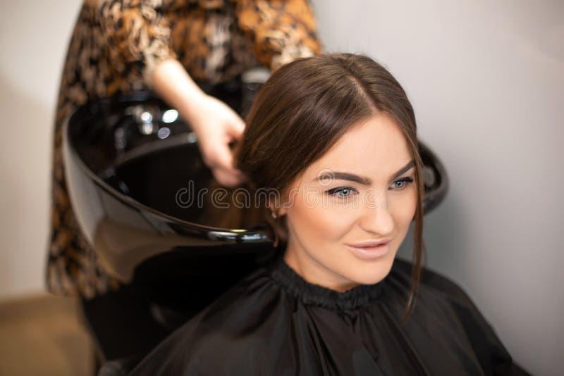 O mestre do corte de cabelo lava o cabelo de seu cliente teve fotos de stock royalty free