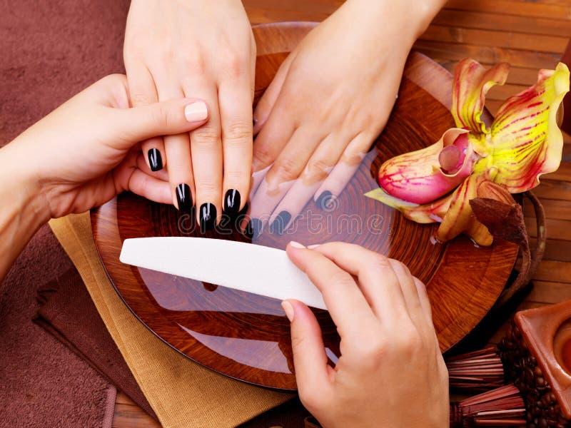 O mestre do manicuro faz o tratamento de mãos nas mãos da mulher imagens de stock
