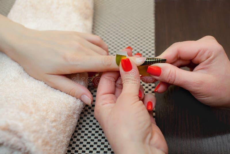 O mestre do verniz para as unhas põe um fixador sobre o dedo antes de fazer o gel dos pregos foto de stock