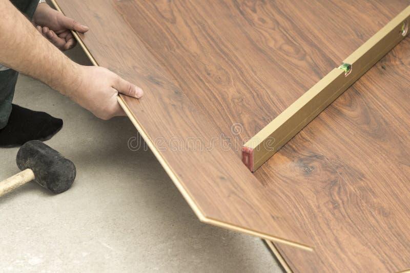 o mestre em luvas azuis faz a colocação floorboard há um nível e martelo de borracha foto de stock royalty free