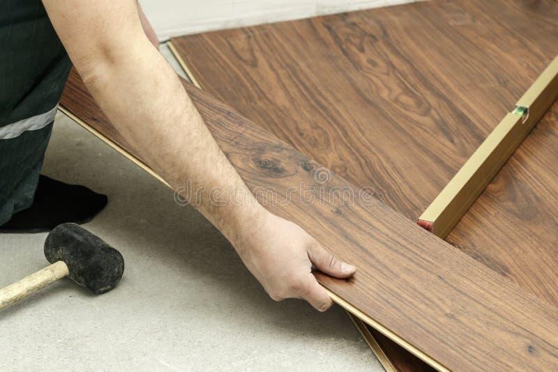 o mestre em luvas azuis faz a colocação floorboard há um nível e martelo de borracha imagem de stock royalty free