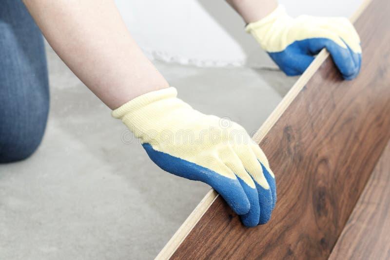 o mestre em luvas azuis faz a colocação floorboard há um nível e martelo de borracha fotos de stock