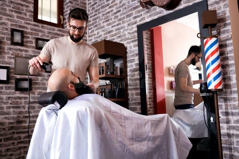 O mestre faz a correção das barbas com ajustador fotos de stock royalty free