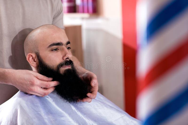 O mestre faz a correção das barbas no salão de beleza do barbeiro imagens de stock royalty free