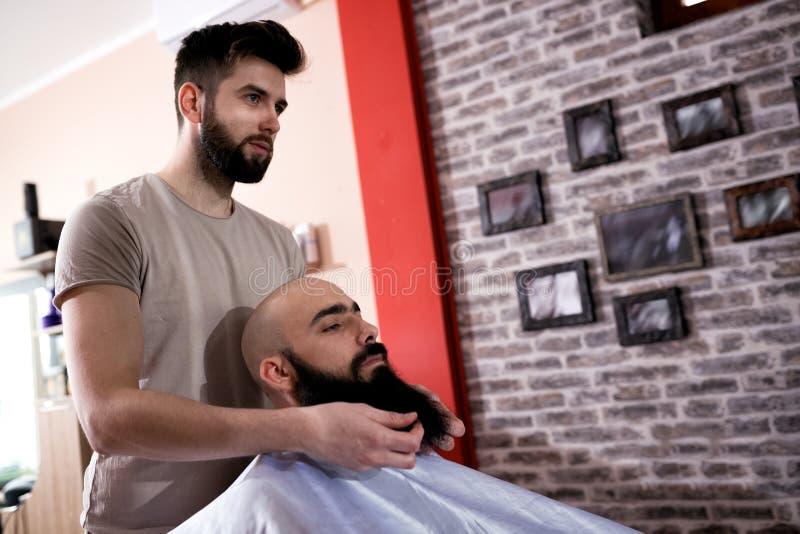 O mestre faz a correção das barbas no salão de beleza do barbeiro fotografia de stock royalty free