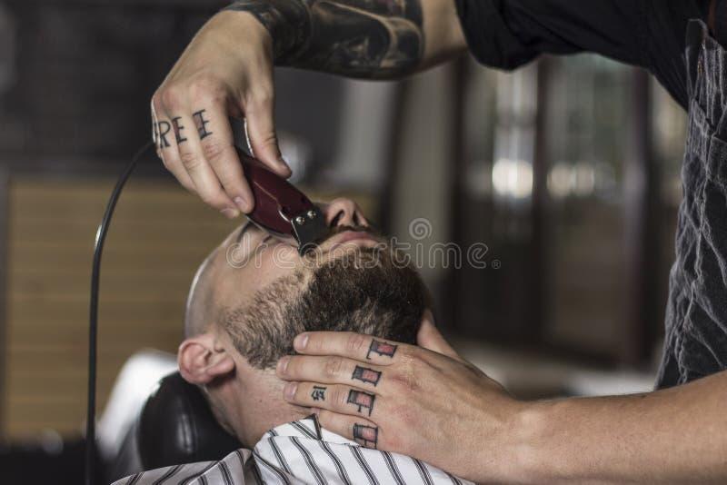 O mestre faz a correção das barbas no salão de beleza do barbeiro Feche acima da foto fotografia de stock royalty free