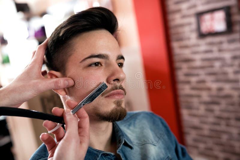 O mestre faz a correção do bigode com uma lâmina imagens de stock royalty free