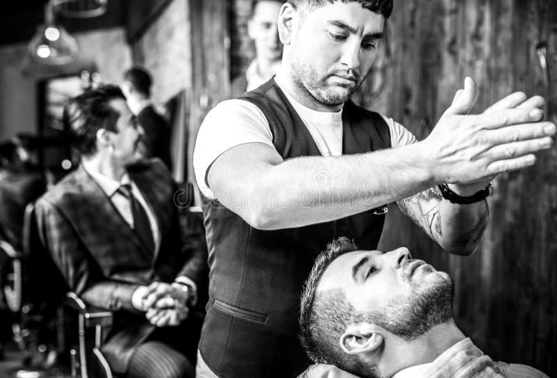 O mestre faz o penteado no salão de beleza do barbeiro fim Preto-branco acima da foto fotografia de stock