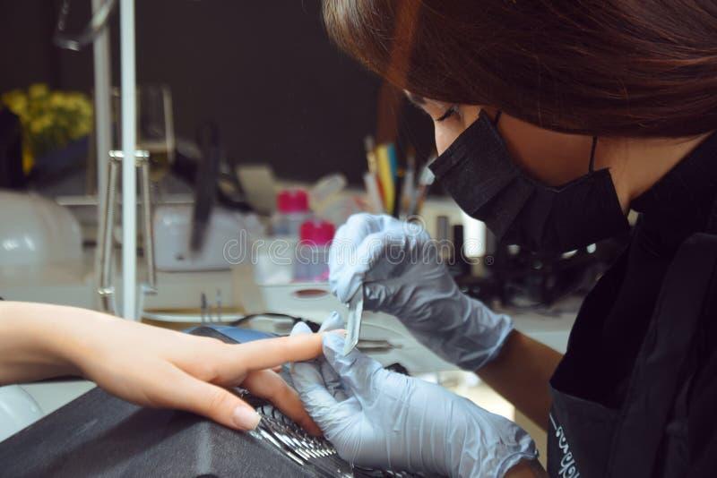 O mestre faz um tratamento de mãos Dia de relaxamento no salão de beleza O mestre do manicuro faz o tratamento de mãos na mão do  imagens de stock royalty free