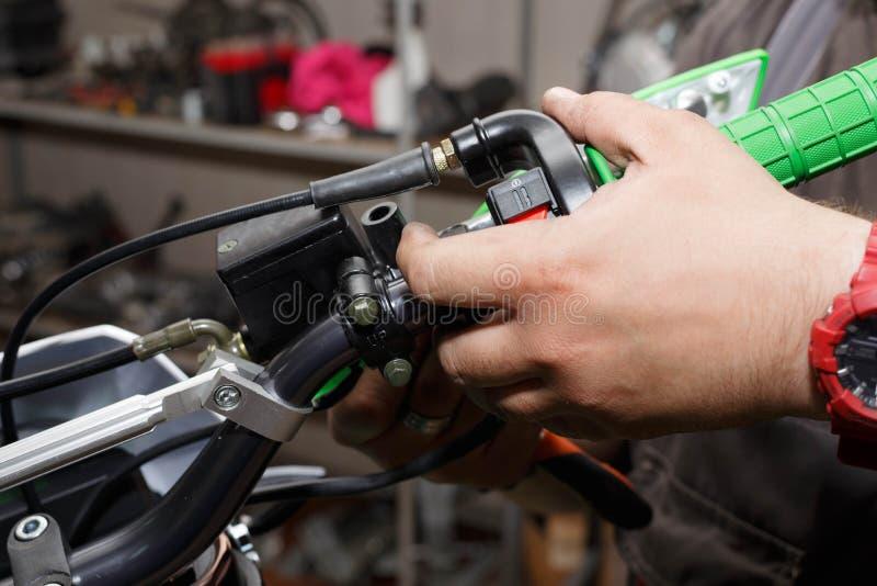 O mestre instala a proteção plástica, assim como a embreagem da motocicleta imagem de stock