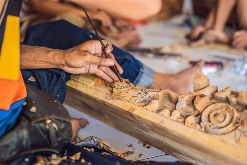 O mestre madeira-Carver fez usando uma faca especial o prato nacional de madeira - uma concha com um punho modelado Um fragmento  imagens de stock