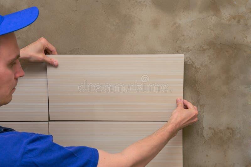 O mestre nos macacões põe azulejos fotos de stock